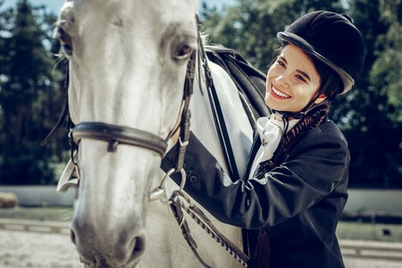 Feeling of love. Positive nice woman feeling happy while being together with her horse