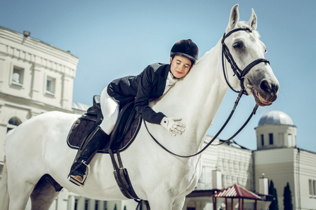 Love to the animal. Delighted young woman hugging her white horse while sitting on it Stock Photo