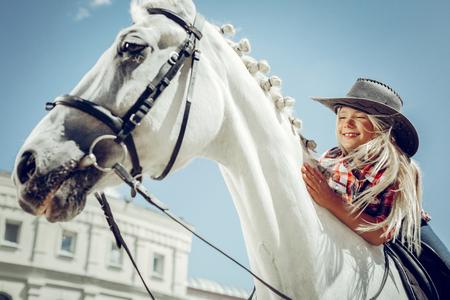 So cute. Joyful blonde girl smiling while stroking her beloved horse