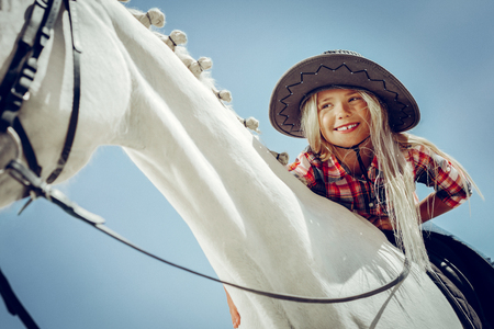 Cute smile. Low angle of a pretty smiling girl while sitting on the white horse