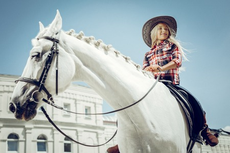 Young horse rider. Low angle of a pretty blonde girl sitting on the horse