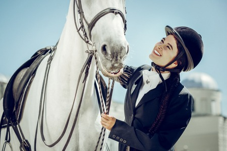 My best friend. Delighted happy woman smiling to her horse while stroking it Stock Photo