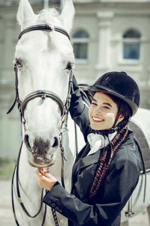 Female rider. Positive young woman feeling happy while standing near her horse