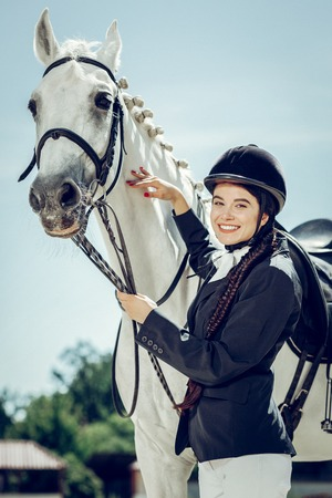 Positive emotions. Delighted nice woman being in a great mood while standing near her horse
