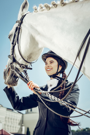 Favourite animal. Low angle of a nice positive woman smiling while standing near her horse Imagens