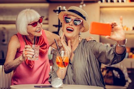 Hippe zonnebril. Aantrekkelijke grijsharige oude vrouwen die foto's maken in een bar terwijl ze verfrissende cocktails drinken Stockfoto