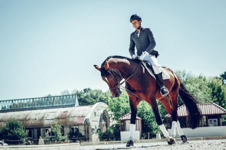 Keeping balance. Pleasant skilled man keeping balance while sitting on the horse back