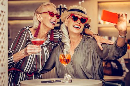 Memory photo. Excited good-looking ladies in funky sunglasses having wide smiles while making selfie