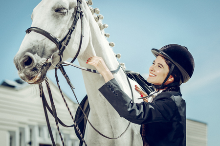 My dear animal. Beautiful young woman smiling while looking at her horse Stock Photo