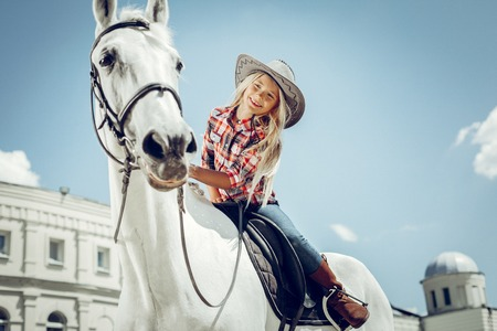 Positive emotions. Positive cute girl looking at her horse while sitting on its back