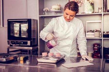Sei leise. Fröhliche junge Frau, die beim Zubereiten von Cupcakes ein Lächeln auf ihrem Gesicht hält Standard-Bild
