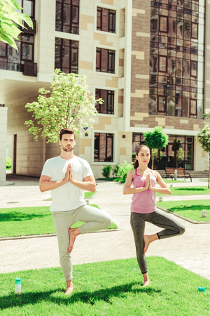Summertime activity. Concentrated bearded man holding hands together while standing in asana