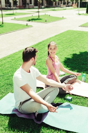 Join us. Cute brunette girl sitting on mat while doing asana with her boyfriend Фото со стока
