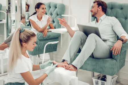 Professional beauty salon. Smiling beautiful woman in white blouse presenting interesting information to her husband while sitting in message salon