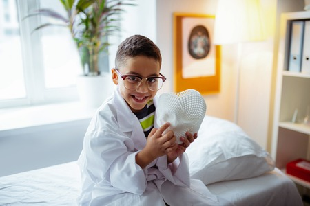 Boy smiling. Little cute boy wearing glasses smiling broadly while working in the hospital of father