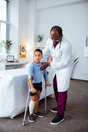 Garçon avec des béquilles. Pédiatre attentionné à la peau foncée aidant un petit garçon à se tenir debout avec des béquilles après s'être cassé le genou