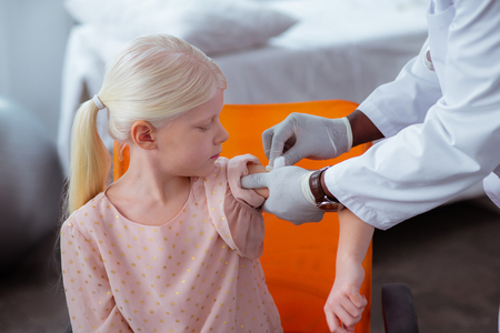 Disinfecting skin. Doctor wearing white gloves disinfecting skin after injection for cute girl Stock Photo
