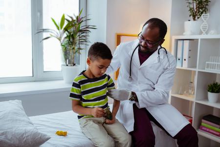 Beruhigender kleiner Junge. Dunkelhäutiger professioneller Kinderarzt, der den süßen kleinen Jungen vor der Injektion beruhigt