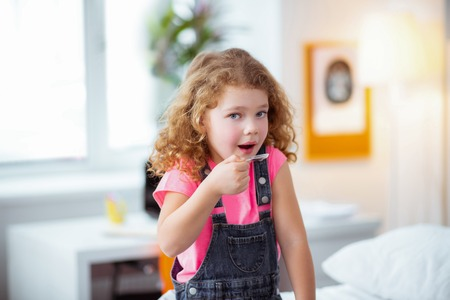 Drinking cough syrup. Curly beautiful little girl drinking cough syrup after visiting pediatrician Stockfoto