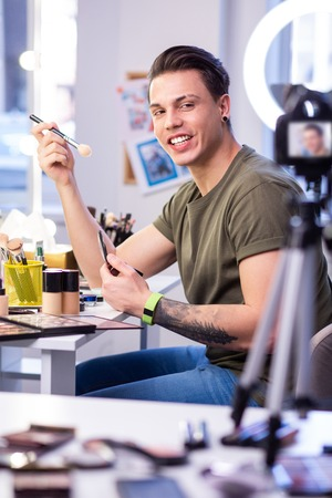Applying makeup. Active skilled man sitting at the beauty table in studio and carrying makeup brush