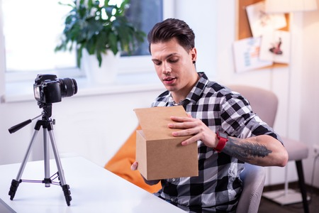 Shooting unpacking video. Interesting dark-haired man glancing inside of the box while sitting in front of switched camera