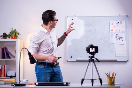 Professional science blogger. Expressive dark-haired man wearing neat white shirt and pointing on the desk with graphics