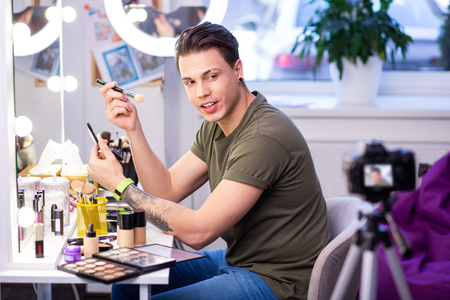 Makeup blogger. Experienced makeup artist with shaved brow looking on professional camera while showing makeup techniques