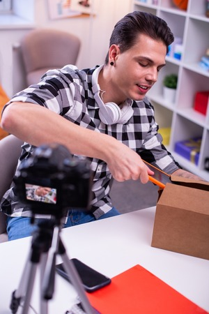 Shooting content . Curious professional video blogger getting tablet from cardboard delivering box while sitting in studio
