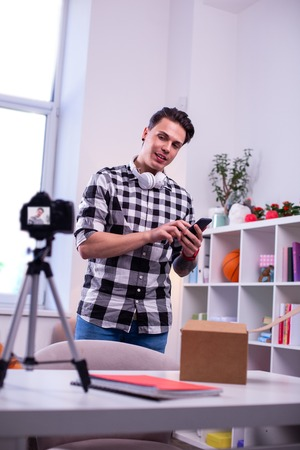 Holding smartphone . Professional video blogger creating content for his channel while standing in light studio Stock Photo