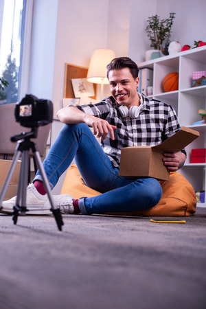 Creating unboxing video. Beaming positive man sitting on the floor during shooting process while holding cardboard box