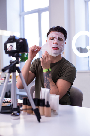 Skincare product. Strong tattooed young man being a professional beauty blogger and testing face treatment