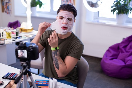 Testing face treatment. Resolute extraordinary man with tattoos uncovering wet mask while caring about his sensitive skin
