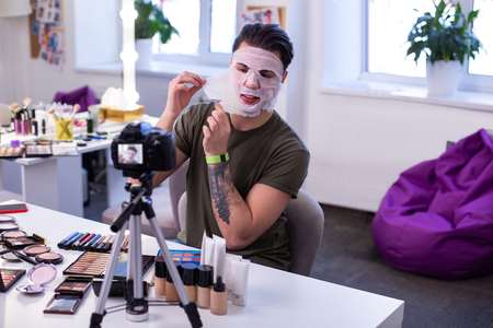 Sensitive skin. Curious communicative guy sitting in front of professional camera and presenting opportunities of face mask Stock Photo