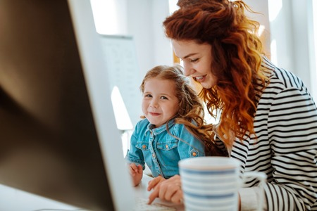 Near lovely daughter. Red-haired successful beautiful freelancer smiling while working near her lovely daughter