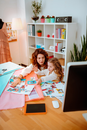 Girl feeling curious. Little funny girl feeling curious visiting red-haired mom working as designer at work Stok Fotoğraf
