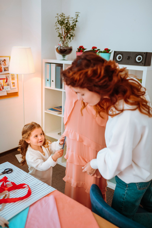 Dress form. Red-haired fashion designer working near dress form with little daughter helping her to make measurement Stockfoto