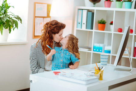 Mother kiss. Red-haired mother kissing her lovely cute daughter joining her at the working table