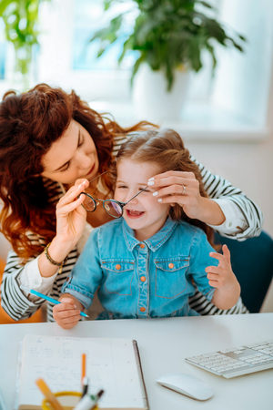 Glasses on. Red-haired mother putting her glasses on little cute daughter while at the working table together 스톡 콘텐츠