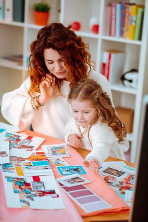 Designer feeling overloaded. Fashion designer feeling overloaded with new collection sitting near daughter