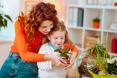 Nice red flowers. Curly mom and cute daughter holding nice red flowers together after taking care of plants