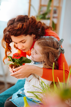 Flowers together. Cute mother and daughter smelling home flowers together after taking care of plants Stockfoto