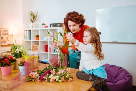 Making floral compositions. Red-haired creative woman making floral compositions looking at flowers with daughter