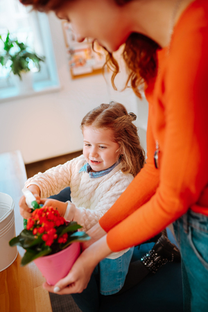 Mother holding flowerpot. Red-haired mother holding flowerpot while daughter watering nice flowers