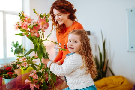 Holding nice flowers. Curly appealing little daughter holding nice flowers while mother making ikebana