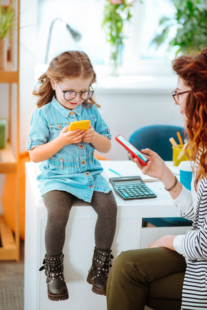 Girl playing game. Funny appealing girl playing game on smartphone sitting near mother checking e-mail
