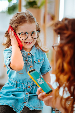 Daughter calling dad. Cheerful beautiful daughter on glasses calling dad while visiting mom at work Stockfoto