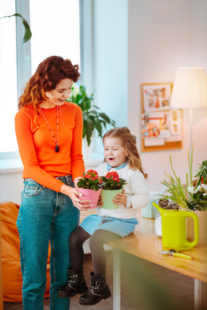 Holding flowerpot. Red-haired mom holding flowerpot standing near her cute stylish daughter sitting on table Stockfoto
