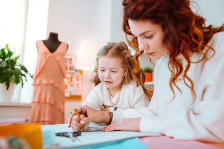 Standing near mother. Appealing cute girl feeling excited while standing near mother designing dresses Banco de Imagens