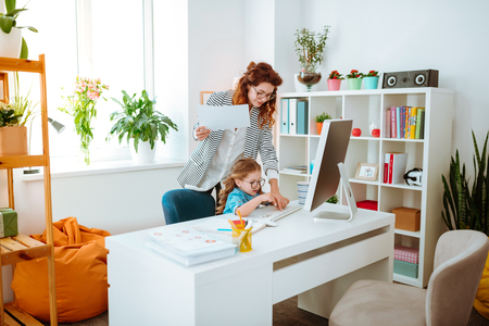 Woman and daughter. Young businesswoman putting her funny daughter at the table in front of computer