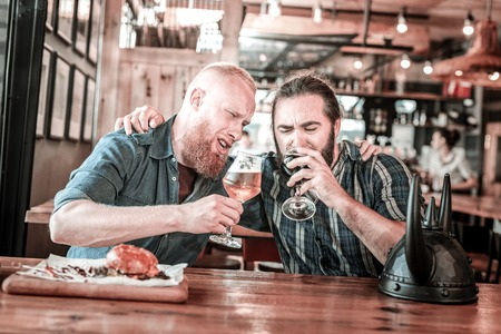 Being supportive. Two unhappy football fans calming ech other and drinking beer in pub. Stock Photo